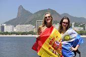 Couple of female sport fans holding the Spanish and Argentinian flag in Rio de Janeiro with Christ t