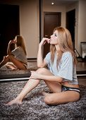 young blond sensual woman sitting on the floor thinking. Beautiful young girl with cosy clothes