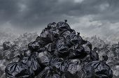 stock photo of environmental pollution  - Garage dump concept with mountains of black waste bags of trash with an unpleasant smell in an infinite landfill heap landscape as a background of environmental damage issues on a foggy dark cloudy scene - JPG