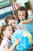 Friendly classmates help to each other to find something at the terrestrial globe. Schooling process