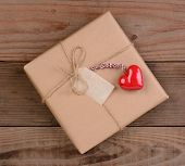 High angle view of a plain brown paper wrapped Valentines Day present with a ceramic red heart. Squa