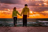 Couple Man And Woman In Love Walking On Beach Seaside Holding Hand In Hand With Beautiful Sunset Sky