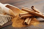 stock photo of cinnamon  - Cinnamon sticks and cinnamon powder in wooden scoop on table - JPG