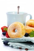 Coffee break with fresh berries and sugary donuts over white background