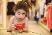 Pretty little girl with red flower stands near pouf in children store.