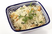 couscous mixed with chopped dried apricots and fresh parsley in a blue and white hand-made tunisian  bowl