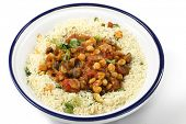 stock photo of tagine  - Chickpeas or garbanzo beans and quartered button mushrooms cooked in a spicy tomato and onion sauce and served with couscous mixed with parsley and dried apricots - JPG