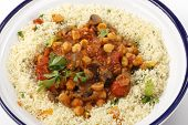 Chickpeas or garbanzo beans and quartered button mushrooms cooked in a spicy tomato and onion sauce and served with couscous mixed with parsley and dried apricots, Moroccan style, served in a bowl