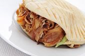 a doner kebab in a plate on a set table