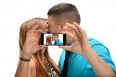 Young couple taking photo with cell phone while kissing isolated over white background