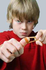 stock photo of prank  - Angry Boy aiming a rubber band - JPG