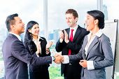 Businesspeople shaking hands in front of flipchart