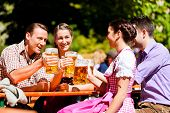 Two happy couple sitting in Bavarian Beer garden and enjoy the beer and the sun