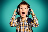 Cute 7 year old boy listening to music on headphones.