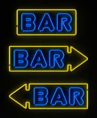 Neon bar sign with and without arrows over dark background