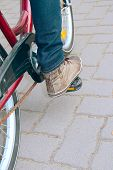 image of pedal  - leg presses the pedal bike photography side view on the street background track of grey stone - JPG