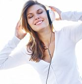 Joyous young girl listens to music through headphones