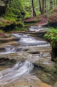stock photo of cave  - Water cascades down a sandstone stream bed in the forest of Ohio - JPG