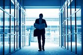Silhouette of business man residing newspaper and walking thru modern office building, in blue tone.