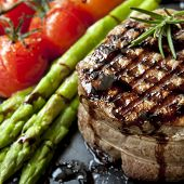 Filet mignon grilled beef steak, with asparagus and cherry tomatoes.  Isolated on white.