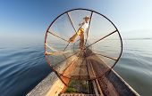 Burma Myanmar Inle lake fisherman on boat catching fish by traditional net. Outdoor photography