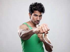 stock photo of knockout  - Handsome Indian man giving a knockout punch