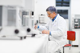 foto of beaker  - Senior male researcher carrying out scientific research in a lab  - JPG