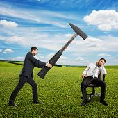 angry boss in the suit holding big hammer and screaming at lazy worker. photo at outdoor