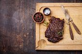 Grilled Ribeye Steak With Salt And Pepper On Meat Cutting Board On Dark Wooden Background