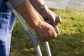stock photo of lame  - closeup of old hands with crutches - JPG