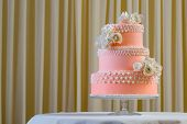 Pink and white wedding cake with individual decoration at withe table
