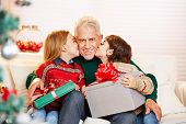 Children kissing grandfather with gifts on the cheek at christmas
