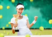 Girl tennis player won the cup at the sport competition. The joy of victory