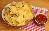 Nacho corn chips and spicy tomato salsa dip