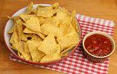 Nacho corn chips and spicy tomato salsa dip
