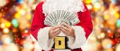 christmas, holidays, winning, currency and people concept - close up of santa claus with dollar money over red lights background