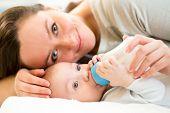 mom feeding baby boy with a milk bottle