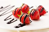 Fresh Strawberries Dipped In Chocolate Sauce On A White Plate.