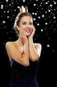 people, holidays, royalty and christmas concept - smiling woman in evening dress wearing golden crown over black snowy background