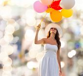 happiness, summer, holidays and people concept - smiling young woman wearing sunglasses with balloons over lights background
