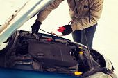 transportation, winter and vehicle concept - closeup of man under bonnet with starter cables