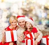 christmas, holidays, family and people concept - happy mother, father and little girl in santa helper hats with gift boxes and sparklers over lights background