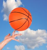 Hand holding a basketball with a beautiful sky behind