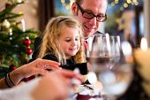 stock photo of wieners  - parents and children toasting with wine and water at Christmas eve dinner  - JPG