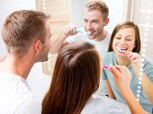 Beauty Young couple in the bathroom brushing teeth together. Happy family cleaning teeth with a tooth brush, looking at their white teeth at the mirror, enjoying their smile. Defocused reflection