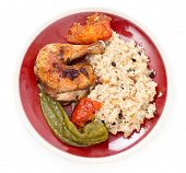 Chicken roasted with tomatoes and long sweet peppers and served with a pilaf