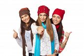 Three girls showing approving gestures pointing at camera