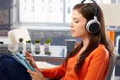 Young woman listening to music on tablet through headphones. Side view.