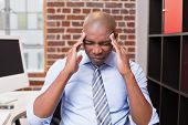Young businessman with severe headache sitting in the office