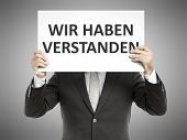 A business man holding a paper in front of his face with the message we understood in german language